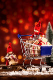 Two festive Christmas dolls out shopping. Two cute little red festive Christmas dolls out shopping on Xmas eve loading their wooden sled with gifts from a royalty free stock photo