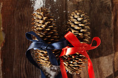 Two festive fir cones on a brown wooden background Stock Photography