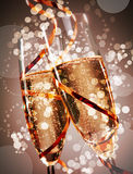 Two festive glasses of bubbly champagne. Two festive flutes of bubbly champagne with sparkling bokeh wound round with a gold party streamer conceptual of a stock photo