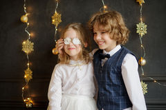 Two festively dressed children photographed for Christmas card. Christmas. Two festively dressed children photographed for Christmas card. Kids tired pose, they Stock Photos
