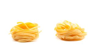 Two fettuccini pasta nests isolated on white. Close up royalty free stock photos