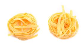 Two fettuccini pasta nests isolated on white. Stock Photos