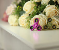 Two fidget spinners pink and green toys on white shelf with flowers on background closeup stock photography