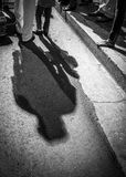 Two figures cast long shadows on a road in cuba. A shodow of a man and a small boy at night in the streets of santiago de cuba Royalty Free Stock Images