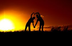 Two figures depict the shape of the heart against the sky at sunset Stock Photos
