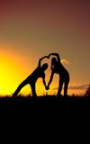 Two figures depict the shape of the heart against the sky at sunset Royalty Free Stock Image