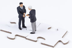 Two figures gives handshake on white puzzle pieces Stock Photography