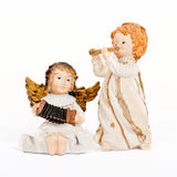 Angelic figurines playing music. Two Figurines of angels playing the accordion and flute on a white background Stock Photo