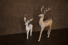 Two figurines of deer - small white and big gold color - stand on a brown table stock photography