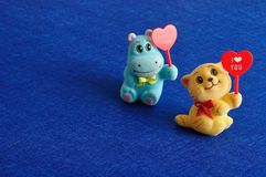 Two Figurines Holding Hearts Stock Photos