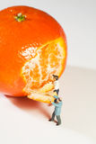 Two figurines peeling an Orange Stock Images
