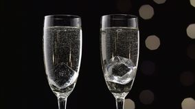 Two filled glasses of champagne with an ice cube in each. Bokeh blinking black background. Close up. Two filled glasses of sparkling champagne with a dipping stock video