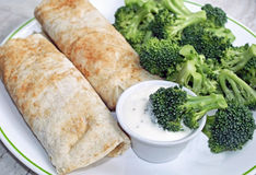 Two filled Tortilla wraps with a side of fresh raw broccoli Stock Photo