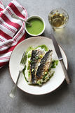 Two fillets of grilled mackerel fish on a plate with mashed potatoes and salsa verde Royalty Free Stock Photos
