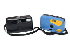 Two film cameras with black wrists straps. one is black while the other is blue in color. Stock Images