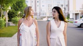 Two fine looking women wearing white dresses are walking down an alley, talking about life and events. Sun is shining stock video