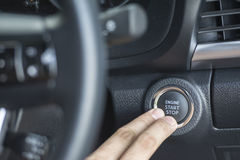 Two Finger pressing the Engine start stop button of a car Stock Photography