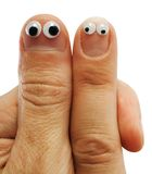 Two fingers. Of hands with doll eyes royalty free stock photos