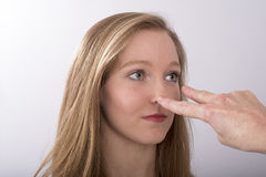 Two fingers point into a teenager's face. A two fingure gesture towards a young woman's eyes stock photography