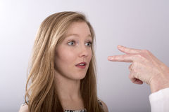 Two fingers point into a teenager's face. A two fingure gesture towards a young woman's eyes royalty free stock photos