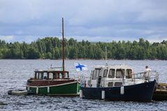 Two Finnish pleasure motor boats in the water area of the port of Kotka. Time of the regatta THE TALL SHIPS RASES Kotka 2017. Kotka, Finland Royalty Free Stock Photography