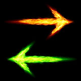 Two fire arrows. Orange and green fire arrows pointing in opposite directions on black background Stock Image