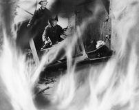 Two fire fighters rescuing a woman royalty free stock images