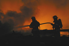 Two firefighters. Are silhouetted by a blaze royalty free stock image