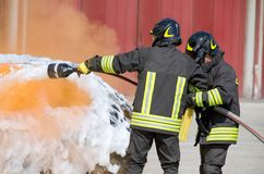 Two firefighters in action with foam Royalty Free Stock Image
