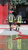 Two firefighters carry the hydrant and hose pipes Stock Photo