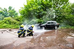 Two firefighters extinguishing a burning car after an accident. Royalty Free Stock Images