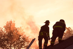 Two firefighters fighting a fire. Firemen risking their lives to protect a buisness in NJ. The firefighters are located on top of a buring building. Smoke is royalty free stock images