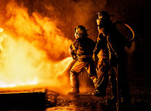 Two firefighters fighting fire with a hose and water Royalty Free Stock Photo