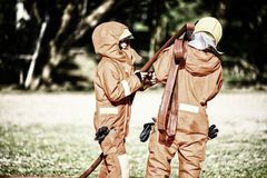 Two firefighters help arrange the water tube to fight the fire. Firefighter prepare dress up and equipment for firefighting. Training,firefighting training stock photo