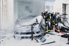 Two Firefighters in intervention on burned car Royalty Free Stock Image