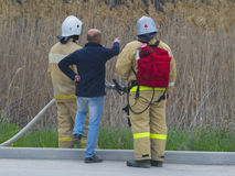 Two firefighters and man showing somewhere Stock Images