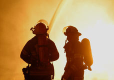 Two firefighters at raging fire stock photo