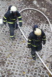 Two firefighters rush to rescue injured people Royalty Free Stock Photos