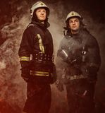 Two firefighters in a smoke stock image