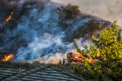 Two Firefighters Stand Next to Bulldozer with Hillside Burning in Background during California Fire. Two firefighters stand next to red bulldozer with smoke and royalty free stock photo