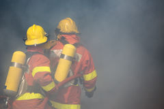 Two firefighters is working surround with smoke and dust Stock Photo