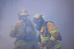 Two Fireman Engulfed in Smoke. Two fireman at the scene of a car fire, engulfed in smoke Stock Image