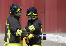 Two firemen in action with foam Royalty Free Stock Photography
