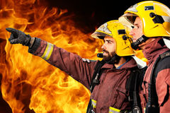 Two firemen analyzing fire. Stock Image