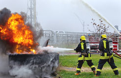 Firefighters fighting a large flame fire. Stock Photo