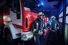Two firemen wearing protective uniform standing next to a fire truck in a garage of a fire department. Two firemen in the fire station garage, standing next to royalty free stock photography