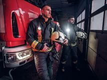 Two firemen wearing protective uniform standing next to a fire truck in a garage of a fire department. Two firemen in the fire station garage, standing next to royalty free stock image