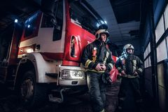 Two firemen wearing protective uniform standing next to a fire truck in a garage of a fire department. Two firemen in the fire station garage, standing next to royalty free stock photos