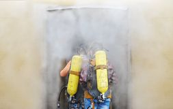 Two firemen with oxygen cylinders in protective suits in protective masks go to a smoke chamber. Two firemen with oxygen cylinders in protective suits in Royalty Free Stock Photo