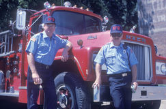 Two firemen standing in front of fire truck Royalty Free Stock Images